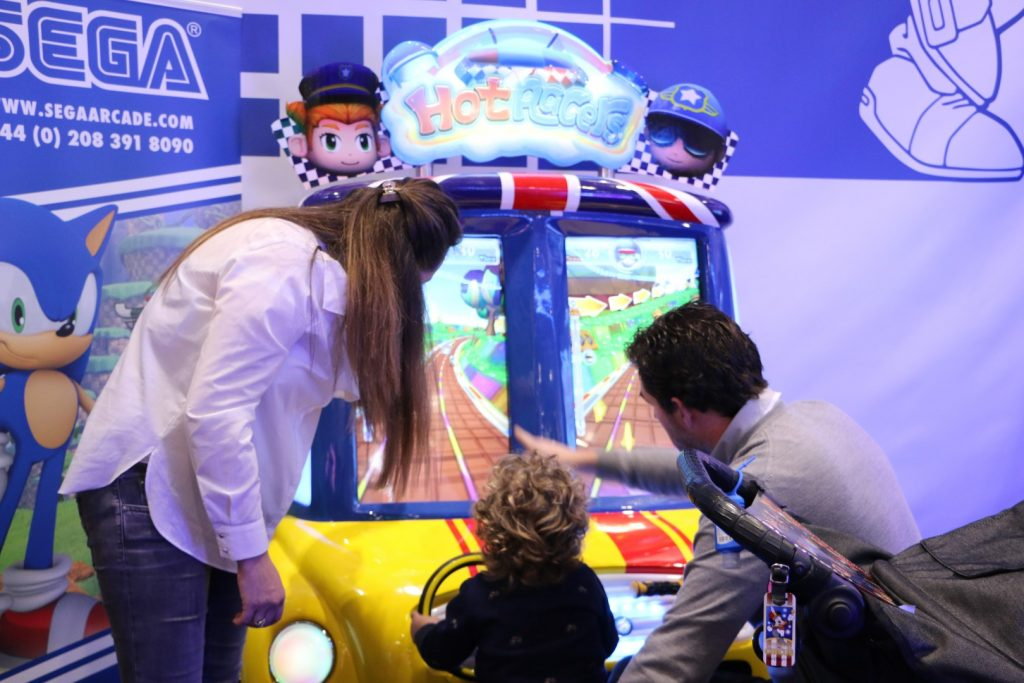 a family of three playing on the Hot Racers arcade amusement two-player driving machine